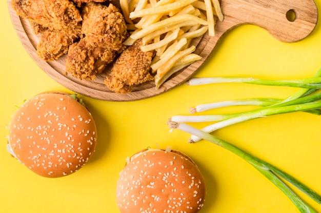 Плоский жареный цыпленок и картофель фри с гамбургерами и зеленым луком