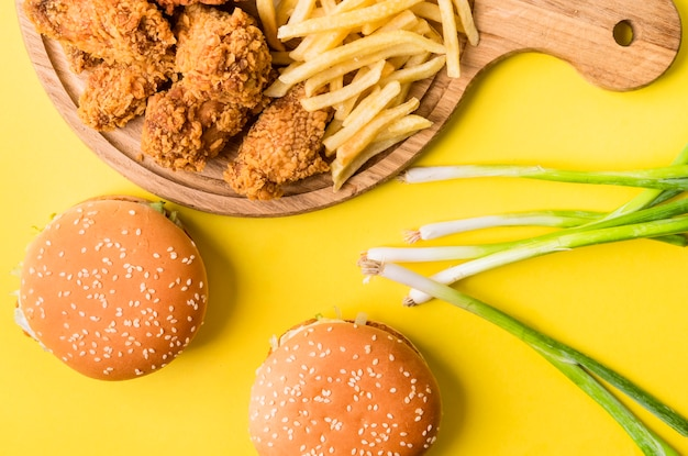 Flat lay fried chicken and fries with burgers and green onions
