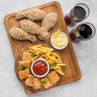 Flat lay of fried chicken legs and nuggets with fizzy drinks and french fries