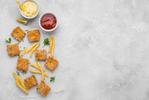 Flat lay of fried chicken nuggets with french fries and copy space