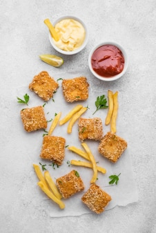 Flat lay of fried chicken nuggets with sauces and french fries