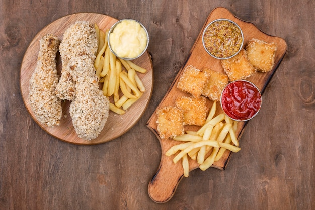 Flat lay of fried chicken with french fries and different types of sauce