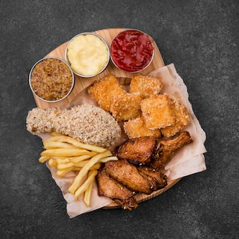Flat lay of fried chicken with variety of sauces