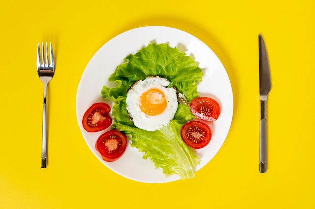 Flat lay fried egg with vegetables dish with cutlery on plain background