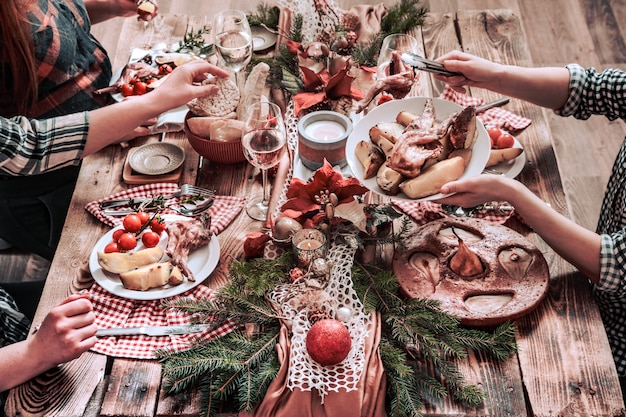 Flat-lay of friends hands eating and drinking together. top view of people having party, gathering, celebrating together at wooden rustic table