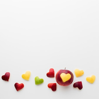Flat lay of fruit heart shapes and apple with copy space