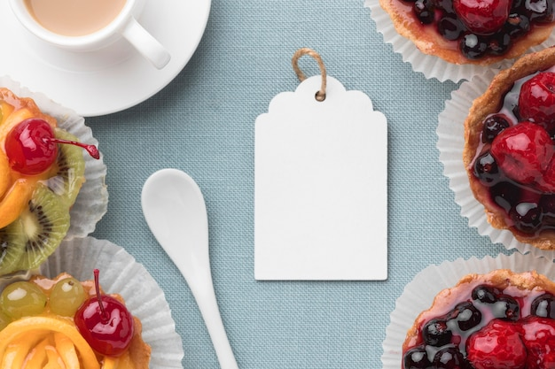 Flat lay of fruit tarts with tag and coffee