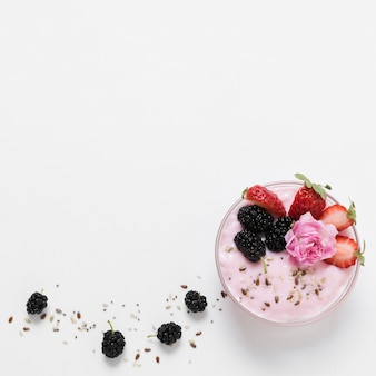 Flat lay of fruit yoghurt with rose