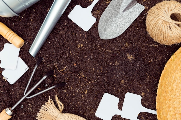 Flat lay gardening tools frame on soil with copy space