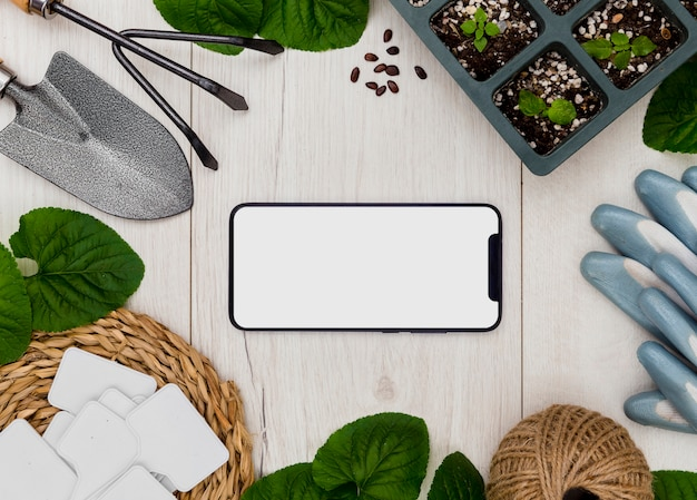 Flat lay gardening tools and plants with blank phone