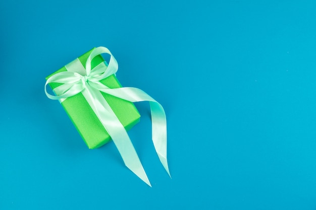 Flat lay of gift box decorated with bow on blue background