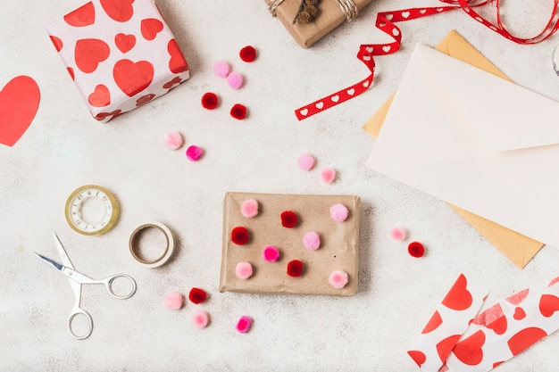Flat lay of gifts with ribbon and pom-poms