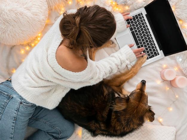派手なベッドでラップトップに取り組んでいる犬とフラットレイの女の子