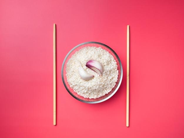 フラットレイ。ピンクの背景にご飯、ニンニク、箸とガラスのボウル。ニンニクのクローブは陰と陽のシンボルの形をしています。