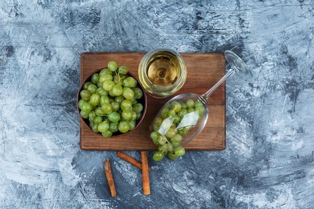 Piatto laici bicchiere di whisky, uva bianca sul tagliere con cannella su marmo blu scuro dello sfondo. orizzontale