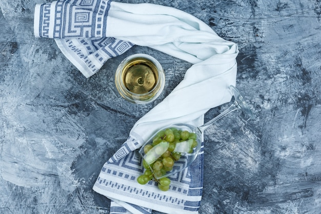 Flat lay glass of white grapes with glass of whisky, kitchen towel on dark blue marble background. horizontal