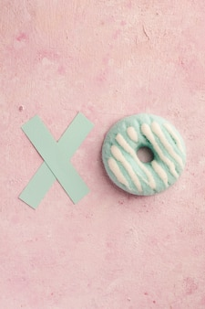 Flat lay of glazed doughnut with the letter x