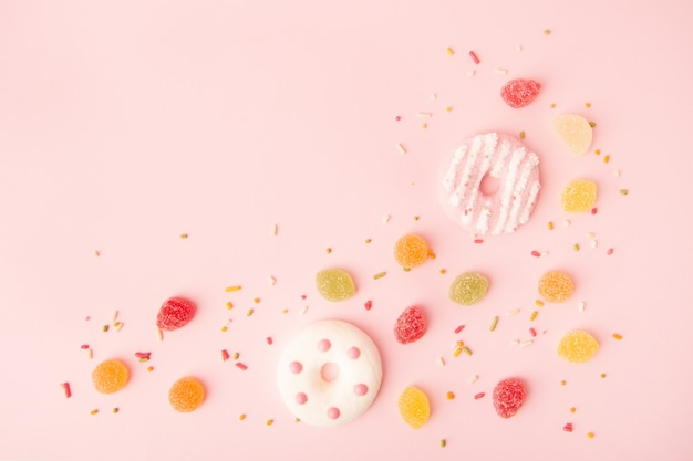 Flat lay of glazed doughnuts with candy and copy space