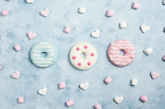 Flat lay of glazed doughnuts with marshmallow and hearts