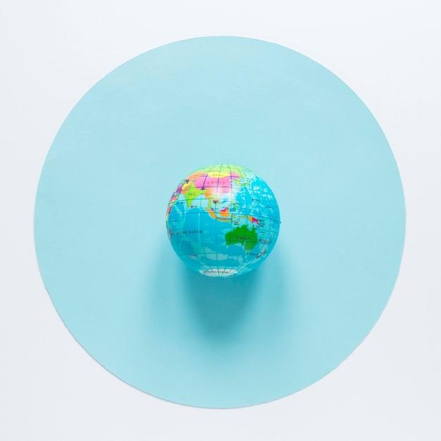 Flat lay of globe on circle