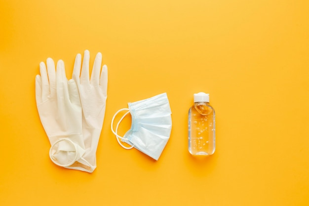 Flat lay of gloves with medical mask and hand sanitizer