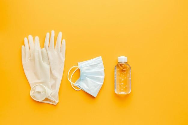 Lay piatto di guanti con mascherina medica e disinfettante per le mani