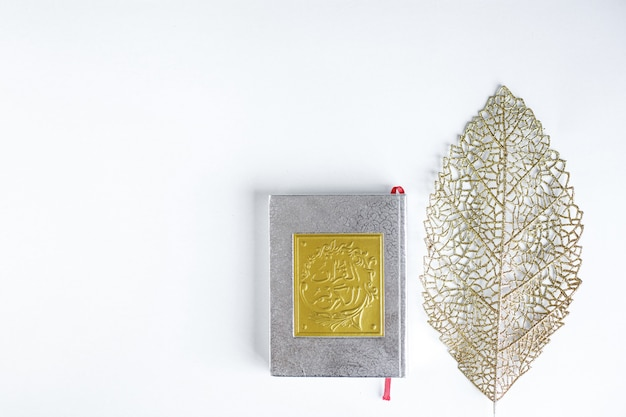 Flat lay gold arabic on book of holy quran and gold leaves on white background with copy space