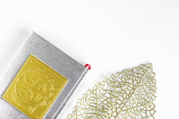Flat lay gold arabic on book of holy quran and gold leaves on white background