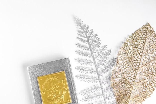 白い背景の上の銀と金の葉と聖クルアーンの本にフラットレイゴールドアラビア語