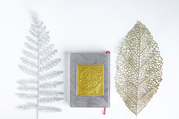 Flat lay of gold holy quran between silver and gold leaves on white background