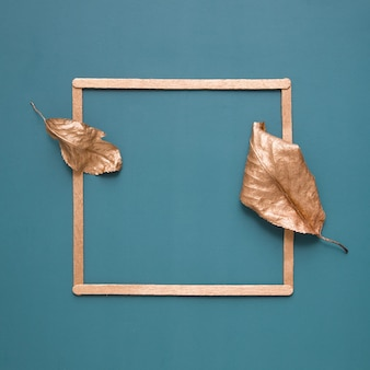 Flat lay of gold leaves and a frame on a turquoise background with copy space. minimalistic concept of harvesting, autumn