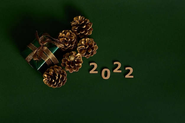 Плоская планировка. золотые сосновые шишки, роскошный подарок в блестящей зеленой оберточной подарочной бумаге с золотым бантом и деревянными цифрами 2022 года, изолированных на темно-зеленом фоне с копией пространства для новогодней и рождественской рекламы