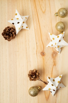 Flat lay of golden christmas ornaments on light wood