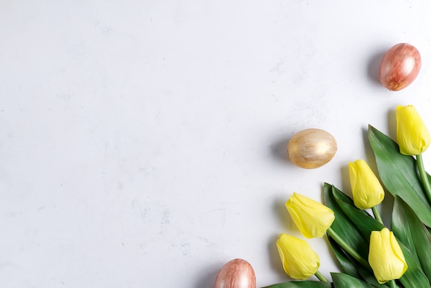 Flat lay of golden easter eggs with tulips on stone marble background. easter background or easter concept.