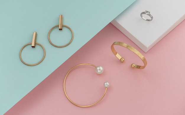 Flat lay of golden jewelries on pastel colors paper background