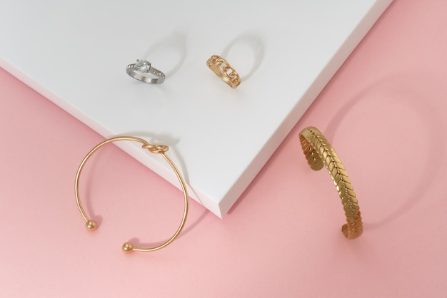 Flat lay of golden knot shape and braid shape bracelets and rings
