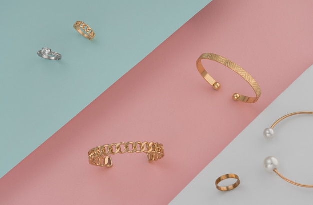 Flat lay of golden and silver jewelries on pastel