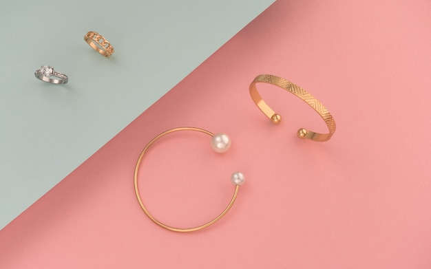 Flat lay of golden and silver rings and bracelets on pink and blue