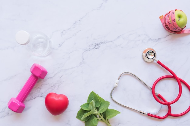 Flat lay of good healthy concept, pink dumbbell with red heart and stethoscope and green apple on white marble background