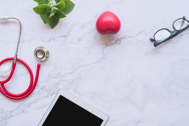 Flat lay of good healthy concept,  red heart and stethoscope and tablet on white marble background