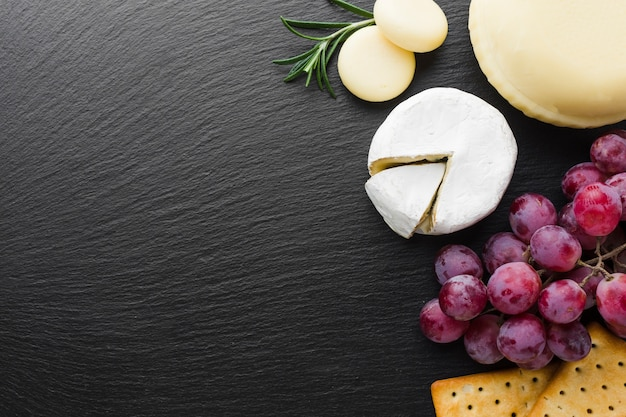 Flat lay gourmet camembert cheese grapes and crackers with copy space