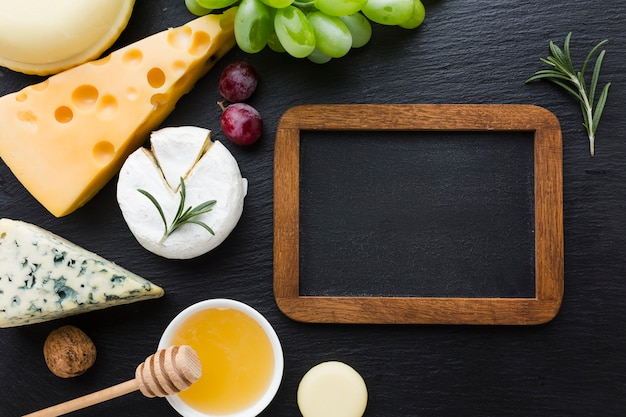 Flat lay gourmet cheese mix and honey with blank blackboard