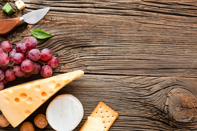 Flat lay grapes emmental and cheese knife with copy space
