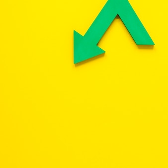 Flat lay green arrow on yellow backgroundwith copy-space
