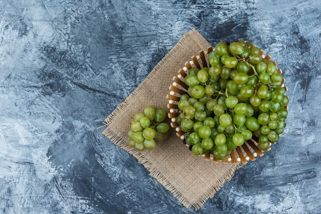 Flat lay green grapes in basket on grunge and piece of sack background. horizontal
