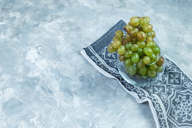 Flat lay green grapes in glass pot on grungy grey and kitchen towel background. horizontal