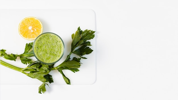 Flat lay green smoothie in glass with lemon