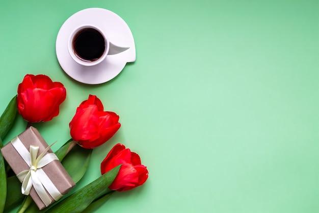 Плоский фон приветствия кофе в чашке красных тюльпанов на зеленом фоне с местом для текста