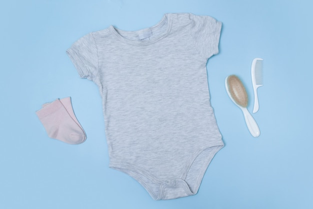 Flat lay grey baby bodysuit on a blue surface