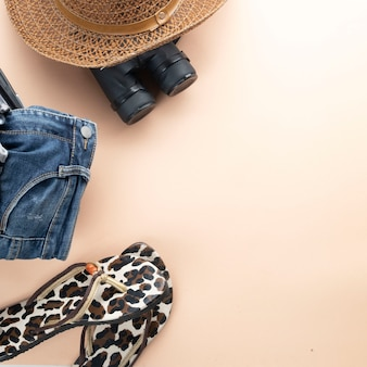 Flat lay grey suitcase with binoculars, hat, jeans and sandles. travel concept